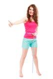 Muchacha de la mujer de la aptitud del deporte con la cinta de la medida que muestra el pulgar para arriba Imagenes de archivo