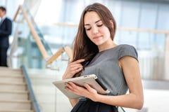 Muchacha de la mujer de negocios que sostiene una tableta Fotos de archivo libres de regalías