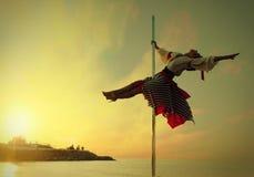 Muchacha de la mujer en danza del polo del ejercicio del vestido contra el mar de la puesta del sol. Fotografía de archivo