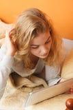 Muchacha de la mujer joven con Internet de la ojeada de la tableta Imagenes de archivo