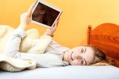 Muchacha de la mujer joven con Internet de la ojeada de la tableta Imagen de archivo
