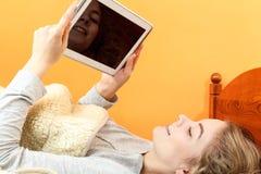 Muchacha de la mujer joven con Internet de la ojeada de la tableta Fotografía de archivo libre de regalías