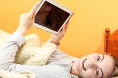 Muchacha de la mujer joven con Internet de la ojeada de la tableta Foto de archivo