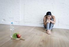 Muchacha de la mujer o del adolescente que se sienta en casa el trastorno alimentario sufridor preocupante solo de tierra de la n Imágenes de archivo libres de regalías