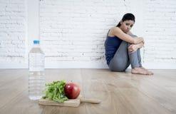 Muchacha de la mujer o del adolescente que se sienta en casa el trastorno alimentario sufridor preocupante solo de tierra de la n Foto de archivo