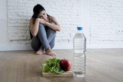 Muchacha de la mujer o del adolescente que se sienta en casa el trastorno alimentario sufridor preocupante solo de tierra de la n Fotografía de archivo