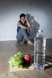 Muchacha de la mujer o del adolescente que se sienta en casa el trastorno alimentario sufridor preocupante solo de tierra de la n Fotos de archivo libres de regalías
