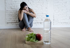 Muchacha de la mujer o del adolescente que se sienta en casa el trastorno alimentario sufridor preocupante solo de tierra de la n Fotografía de archivo libre de regalías