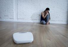 Muchacha de la mujer o del adolescente que se sienta en solo de tierra preocupante en casa Fotos de archivo