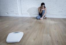 Muchacha de la mujer o del adolescente que se sienta en solo de tierra preocupante en casa Fotografía de archivo libre de regalías
