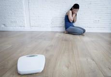 Muchacha de la mujer o del adolescente que se sienta en solo de tierra preocupante en casa Fotografía de archivo