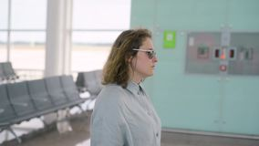 Muchacha de la mujer que camina en el terminal de aeropuerto, de la maleta trasera del balanceo almacen de metraje de vídeo