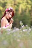 Muchacha de la naturaleza que se sienta en el campo de Wildflowers Fotografía de archivo libre de regalías