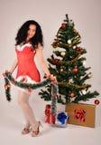 Muchacha de la Navidad con el árbol y los presentes, vestidos en el traje de Santa Claus Foto de archivo libre de regalías