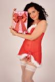 Muchacha de la Navidad con el presente, vestido en el traje de Santa Claus Foto de archivo libre de regalías