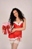 Muchacha de la Navidad con el presente, vestido en el traje de Santa Claus Imágenes de archivo libres de regalías