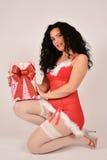 Muchacha de la Navidad con el presente, vestido en el traje de Santa Claus Foto de archivo