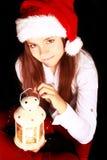 Muchacha de la Navidad con la linterna de la iluminación sobre obscuridad Foto de archivo libre de regalías