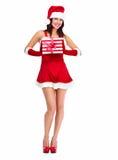 Muchacha de la Navidad del ayudante de Papá Noel con un presente. Imagen de archivo