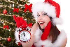 Muchacha de la Navidad en el sombrero de santa, árbol de abeto, reloj de alarma Fotografía de archivo libre de regalías