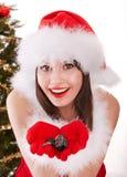 Muchacha de la Navidad en el sombrero de santa con el árbol de abeto. Fotografía de archivo