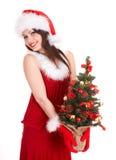 Muchacha de la Navidad en el sombrero de santa con el pequeño árbol. foto de archivo libre de regalías