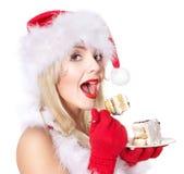 Muchacha de la Navidad en el sombrero de santa que come la torta. Foto de archivo libre de regalías