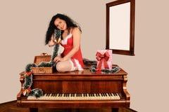 Muchacha de la Navidad en piano, en el traje de Papá Noel con los regalos Imágenes de archivo libres de regalías