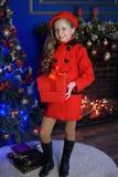 Muchacha de la Navidad en una boina y una capa rojas Fotos de archivo libres de regalías