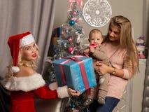 Muchacha de la Navidad que da presentes al pequeño bebé Mujer vestida como Papá Noel foto de archivo