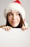 Muchacha de la Navidad que oculta detrás de una tarjeta en blanco Fotografía de archivo