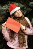 Muchacha de la Navidad que sostiene la tarjeta roja Fotografía de archivo libre de regalías