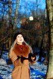 Muchacha de la nieve que se divierte el invierno, juego con la bola de nieve Fotos de archivo libres de regalías