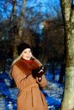 Muchacha de la nieve que se divierte el invierno, mirando en bola de nieve Fotografía de archivo libre de regalías