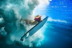 Muchacha de la persona que practica surf bajo ola oceánica foto de archivo