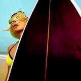Muchacha de la persona que practica surf con el tablero de resaca elegante en la playa Tiempo que practica surf imagenes de archivo