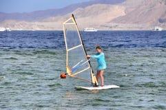 Muchacha de la persona que practica surf del viento Imagen de archivo libre de regalías
