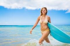 Muchacha de la persona que practica surf en bikini con la tabla hawaiana Fotos de archivo libres de regalías