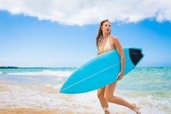 Muchacha de la persona que practica surf en bikini con la tabla hawaiana Foto de archivo libre de regalías