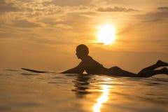 Muchacha de la persona que practica surf en el océano en el tiempo de la puesta del sol Imagen de archivo