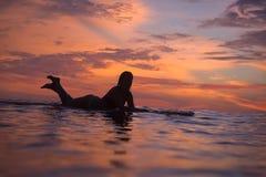 Muchacha de la persona que practica surf en el océano en el tiempo de la puesta del sol Imagenes de archivo