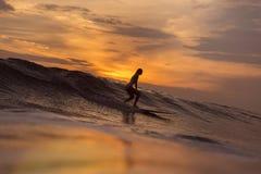 Muchacha de la persona que practica surf en el océano en el tiempo de la puesta del sol Foto de archivo libre de regalías