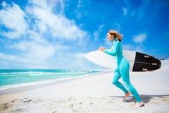 Muchacha de la persona que practica surf en la playa Foto de archivo libre de regalías