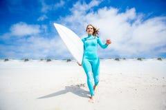 Muchacha de la persona que practica surf en la playa Fotos de archivo