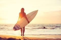 Muchacha de la persona que practica surf en la playa en la puesta del sol Imagen de archivo libre de regalías