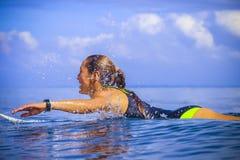 Muchacha de la persona que practica surf en onda azul asombrosa Imagen de archivo