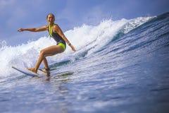 Muchacha de la persona que practica surf en onda azul asombrosa imagenes de archivo