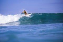 Muchacha de la persona que practica surf en onda azul asombrosa Foto de archivo
