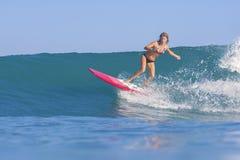 Muchacha de la persona que practica surf en onda azul asombrosa Fotografía de archivo libre de regalías