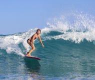 Muchacha de la persona que practica surf en onda azul asombrosa Imágenes de archivo libres de regalías